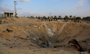 """Palestinians inspect a huge hole after Israeli airstrikes hit the residential area of Deir al Balah, Gaza, on Friday. The Israeli military says it is """"currently striking Hamas terror targets"""" in Gaza."""