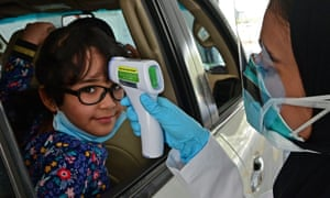 A nurse measures the body temperature of a young girl at a drive-through testing centre for coronavirus in Abu Dhabi.