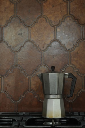 A coffee pot on top of the hob with a spanish tile splashback in the background