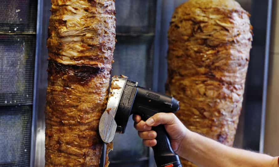 A man slices cuts of meat from a doner spit in Frankfurt, Germany.