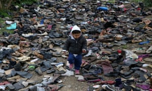 A boy walks among pairs of shoes at the premises of an NGO next to the Moria camp for refugees and migrants, on the island of Lesbos, Greece, 9 March 2020.