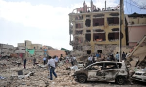 People walk among the rubble of the hotel attack in Mogadishu.