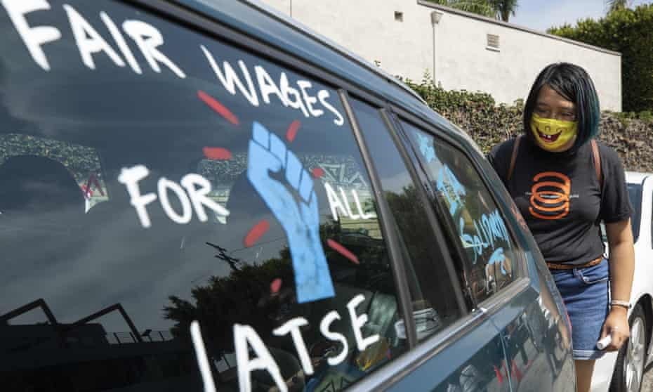 Crystal Kan, a storyboard artist, draws pro-labor signs on cars of union members during a rally at the Motion Picture Editors Guild IATSE Local 700 on Sunday in Los Angeles.