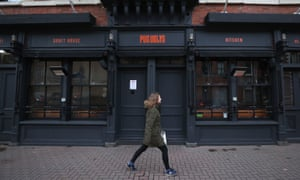 A woman walks past a closed bar in Belfast during Northern Ireland's national lockdown.