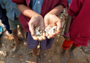 A girl shows some of the mica flakes she has collected while working in an illegal mine in Jharkhand, India