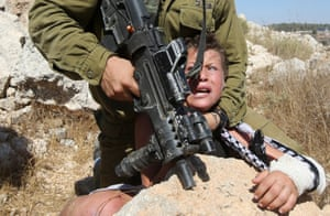 <strong>Nabi Saleh, West Bank</strong> An armed Israeli soldier restrains a young boy during clashes with Palestinians protesting against Palestinian land confiscation to expand the Jewish Hallamish settlement near Ramallah.