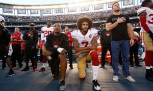 Kaepernick (right) alonside teammate Eric Reid kneel for the US national anthem.