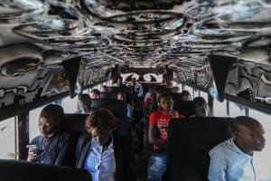 Passengers ride a matatu named 'Batman' during rush hour