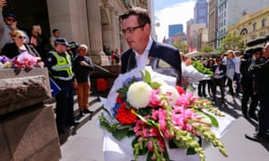 Premier Daniel Andrews lays flowers at Bourke Street mall on Saturday.