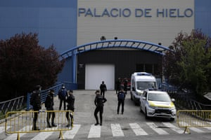 Police officers stand in front of an ice rink turned into a temporary morgue in Madrid, Spain, on 24 March.