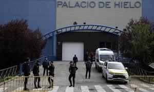 Des policiers se tiennent devant la patinoire de Madrid, qui a été transformée en morgue temporaire