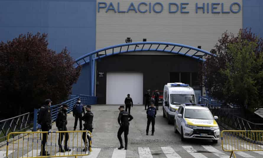 Police officers stand in front of Madrid's ice rink, which has been turned into a temporary morgue