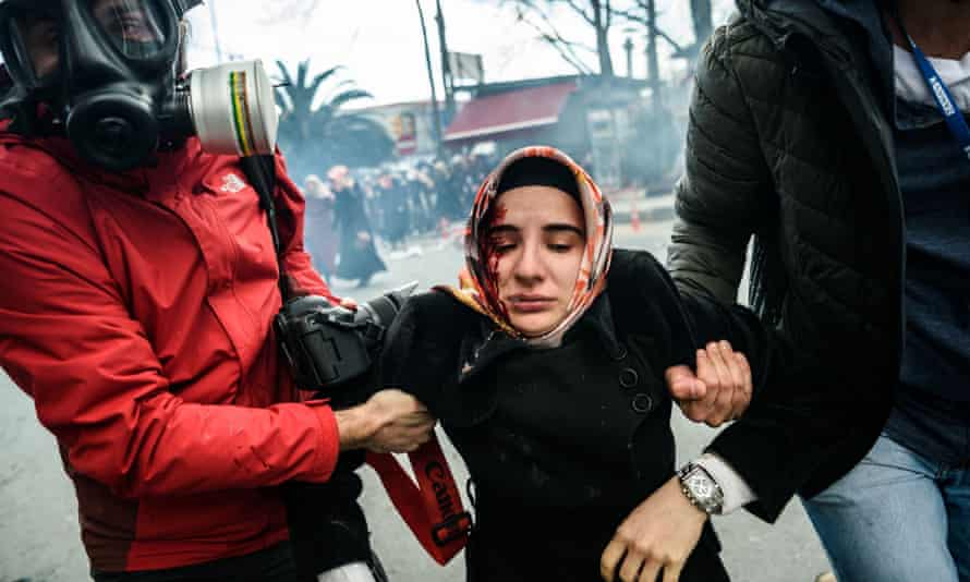 Journalists carry an injured woman after Turkish riot police used tear gas to disperse protesters at the closure of the daily newspaper.