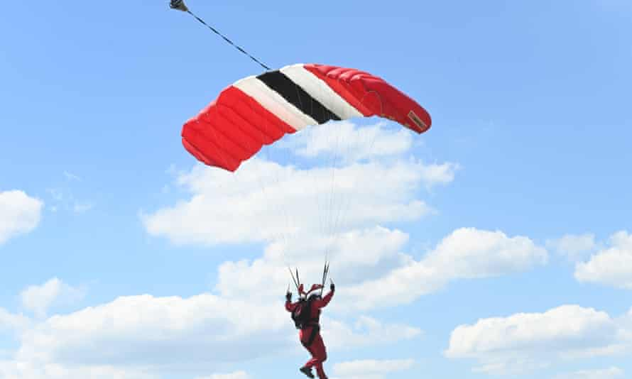 """A member of the British army's parachute regiment lands on the course during """"Derby day"""" of the Derby Festival in Epsom, Britain, 05 June 2021."""