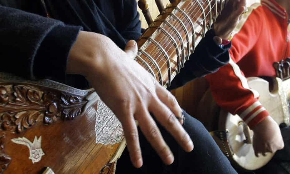 Close up of a girl playing a sitar in her lap, wit only her hands and the body of the instrument rvisible