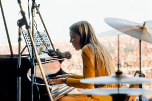 Joni Mitchell – survives a tough crowd'The perfect photograph, in what was an ordeal. Joni had been asked to come on stage early as the programme was running late. During her set, she had to stop and ask for a doctor as a person in the audience was taken ill. Then a man tried to take her microphone to make a speech. Joni made an impassioned appeal to the audience to respect the musicians. She eventually won over the crowd'