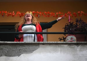 A woman sings from her balcony in the Italian capital