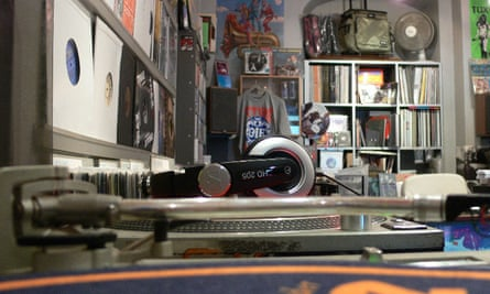 A set of headphones lie next to a turntable amid the vinyl collection in the Side One record shop in Warsaw, Poland.