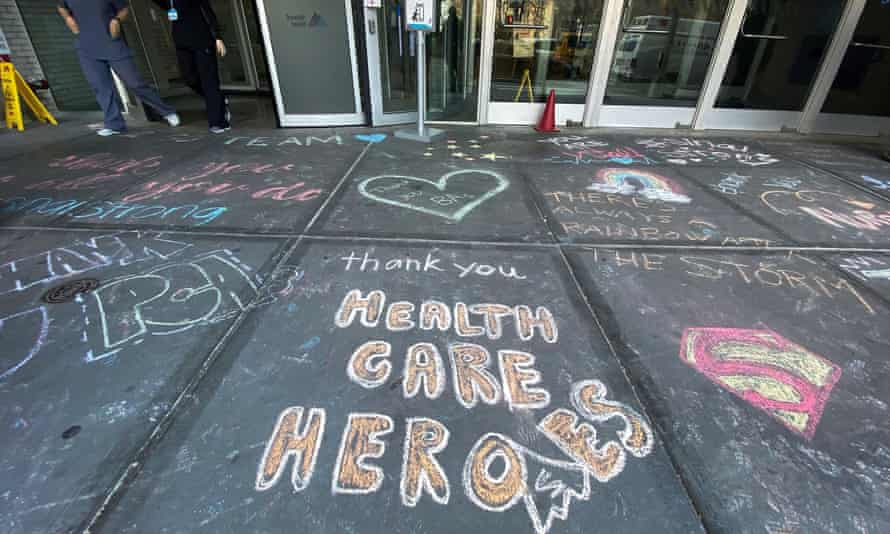 Healthcare workers exit Mount Sinai hospital past messages of thanks written on the sidewalk in New York City.