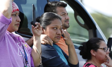 Friends, coworkers and family watch as US immigration officials raid the Koch Foods Inc plant in Morton, Mississippi, on Wednesday.