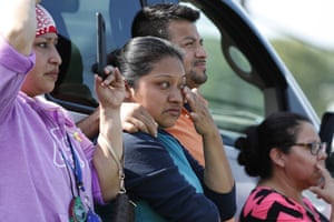 Friends, coworkers and family watch as US immigration officials raid a Koch Foods plant in Morton.