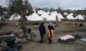 Migrants walk in a field outside the camp of Moria, Lesbos, Greece on February 10, 2016.