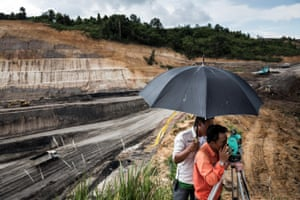 Surveyors measure and mark land to expand a quarry at a mining concession in Makroman, East Kalimantan, Indonesian Borneo