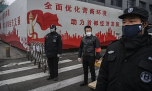 Security guards control access to a residential area of Beijing, China, on Thursday to help fight the spread of coronavirus.