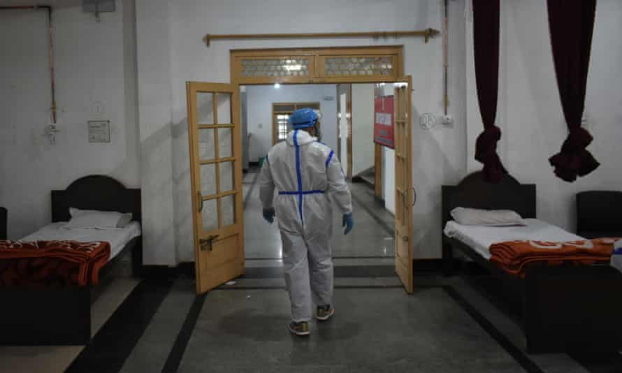 A health worker inspects beds at a temporary Covid-19 hospital in Srinagar