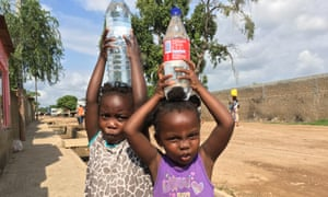 Girls carry bottled water in Maputo, where a drought has reversed progress in improving access to water.
