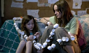 Jacob Tremblay and Brie Larson as a mother and son, sitting close together stringing egg shell halves together, in Room.
