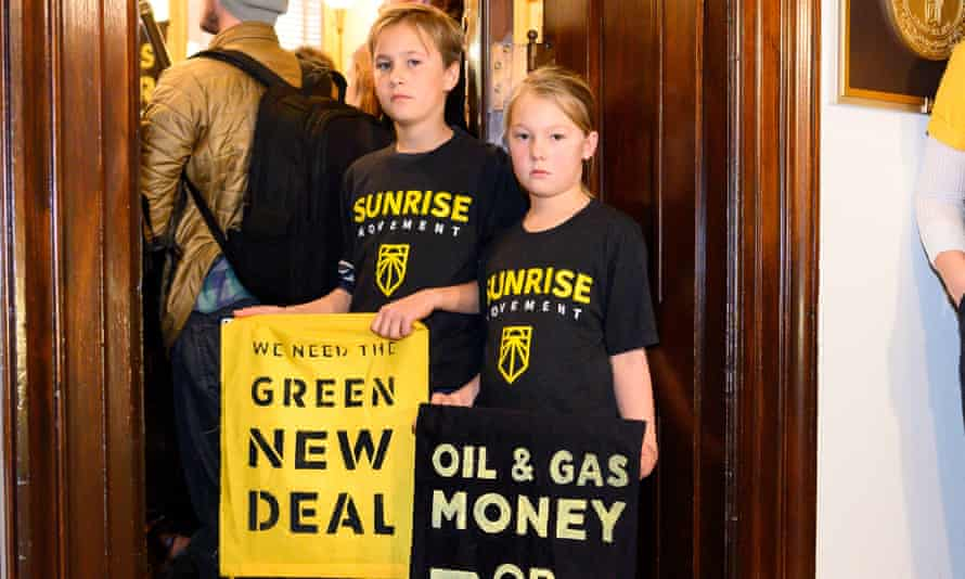 Young protestors hold placards at the office of U.S. Senator Mitch McConnell during a Green New Deal demonstration.