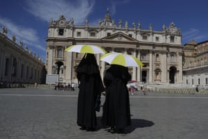 Vatican City Nuns shelter from the sun with their umbrellas bearing the colours of the Vatican flag prior to the start of Pope Francis Angelus prayer in St Peter's Square