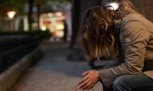 girl huddled over in the street
