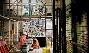 Workmen and scaffolding in front of Eduardo Paolozzi's Church Window mosaic at Tottenham Court Road station.