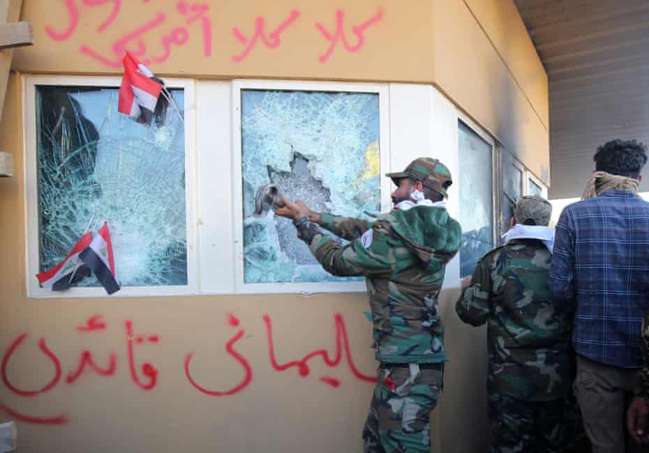 Members the Hashed al-Shaabi, a mostly Shiite network of local armed groups trained and armed by powerful neighbour Iran, smash the bullet-proof glass of the US embassy's windows in Baghdad.