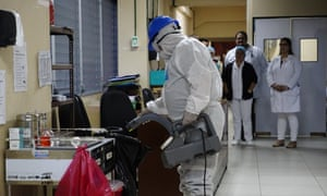 A disinfection worker wearing protective gears sprays anti-septic solution against the coronavirus in San Salvador, El Salvador.