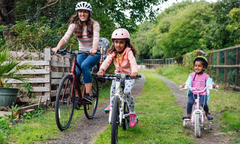 Mother and her two young daughters riding their bikes around a public park during the Covid-19 pandemic