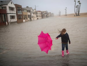 A child walks through floodwaters near a pier in California. The climate crisis can expose millions to flooding.
