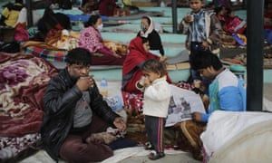 Survivors of Saturday's earthquake drink tea as they wake up after spending the night in open ground for fear of more tremors