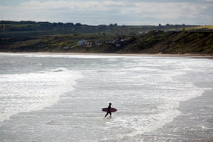 May 2020: a lone surfer walks through the sea as he returns to the shore at Filey
