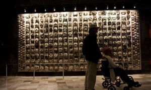A man pushes a woman in a wheelchair past a wall of ancient stone skulls, excavated at Templo Mayor, that represent sacrificial victims, at the entrance to the Templo Mayor museum in central Mexico City, Friday, Aug. 7, 2015. In the pantheon of Mexico's pre-Hispanic gods, most Aztec dieties are depicted as brutal, blood-thirsty gods, only appeased by human sacrifices. But the Templo Mayor museum has put on display for the first time an offering dedicated to Xochipilli, the Aztec god of singing, dancing, and the morning sun. The offering was found in 1978 during excavations of the Red Temple, a small altar adjacent to Templo Mayor.(AP Photo/Rebecca Blackwell)