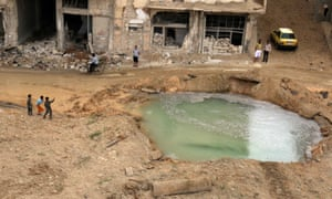 People inspect a water-filled hole at the site of an airstrike on the rebel-held Tariq al-Bab neighbourhood of Aleppo.