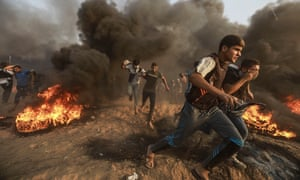 Palestinian protesters run to take cover from teargas fired by Israeli troops during clashes on the Gaza-Israel border.