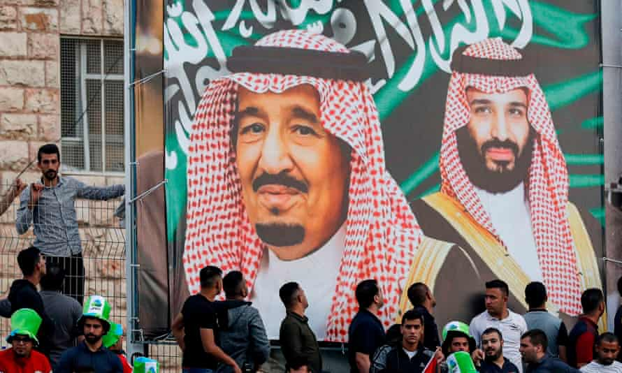 Saudi football fans stand beneath a banner depicting King Salman bin Abdulaziz and his son Crown Prince Mohammed bin Salman.