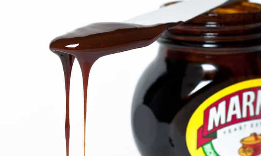 Knife with dripping marmite on top of a jar