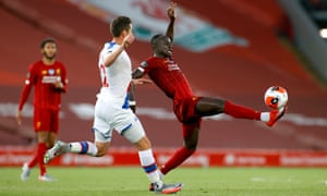 Sadio Mane of Liverpool controls the ball as Joel Ward of Crystal Palace looks on.