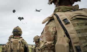 A military exercise on Salisbury Plains in July 2020 near Warminster, England, soldiers seen from the rear observe an air drop