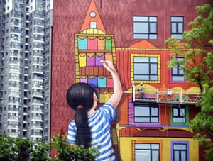 Nanjing, China: A lifelike mural of a child painting a building is cleaned by workers on a scaffolding. The illustration, on the wall of Jiangsu women and children's healthcare hospital, is part of a scheme that uses art to promote healing and wellbeing