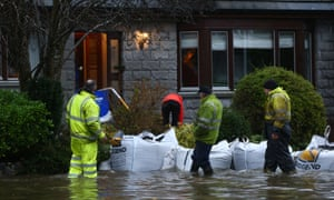 Council workers and sandbags next to a flooded house.